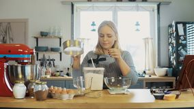 Νέα ξανθή γυναίκα που χρησιμοποιεί τις κλίμακες κουζινών στο ζύγισμα του αλευριού Όμορφο θηλυκό που ψήνει τα cupcakes στην κουζίν απόθεμα βίντεο