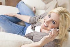 Νέα ξανθή γυναίκα που χρησιμοποιεί το τηλέφωνο κυττάρων στο σπίτι στον καναπέ στοκ φωτογραφία με δικαίωμα ελεύθερης χρήσης