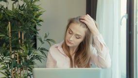 Νέα ξανθή γυναίκα που χρησιμοποιεί το φορητό προσωπικό υπολογιστή καθμένος στον πίνακα απόθεμα βίντεο