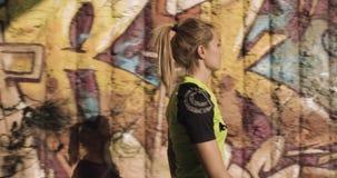 Νέα ξανθή γυναίκα στην ένδυση ικανότητας που περπατά κοντά grunge στον τοίχο γκράφιτι Πλευρά μετά από την άποψη θερινό ηλιόλουστο φιλμ μικρού μήκους