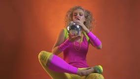 Νέα ξανθή γυναίκα στην εξάρτηση, τη συνεδρίαση και το παιχνίδι της δεκαετίας του '80 με μια σφαίρα disco, πορτοκαλί υπόβαθρο απόθεμα βίντεο