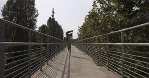 Νέα ξανθή γυναίκα στην τρέχοντας κατάρτιση ένδυσης ικανότητας στην εναέρια διάβαση πεζών Μπροστινός μετά από την άποψη θερινό ηλι φιλμ μικρού μήκους