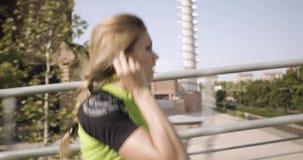 Νέα ξανθή γυναίκα στην τρέχοντας κατάρτιση ένδυσης ικανότητας στην εναέρια διάβαση πεζών Πλευρά μετά από την άποψη θερινό ηλιόλου απόθεμα βίντεο