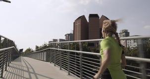 Νέα ξανθή γυναίκα στην τρέχοντας κατάρτιση ένδυσης ικανότητας στην εναέρια διάβαση πεζών Πίσω μετά από την άποψη θερινό ηλιόλουστ απόθεμα βίντεο