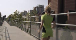 Νέα ξανθή γυναίκα στην τρέχοντας κατάρτιση ένδυσης ικανότητας στην εναέρια διάβαση πεζών Πίσω μετά από την άποψη θερινό ηλιόλουστ φιλμ μικρού μήκους