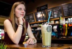 Νέα ξανθή γυναίκα στον τοπικό καφέ στα ξύλινα WI επιτραπέζιων ποτών frappe Στοκ φωτογραφία με δικαίωμα ελεύθερης χρήσης
