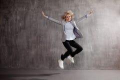 Νέα ξανθή γυναίκα στο επιχειρησιακό κοστούμι και πάνινα παπούτσια που πηδούν για τη χαρά, γκρίζο κατασκευασμένο υπόβαθρο στοκ εικόνες