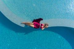 Νέα ξανθή γυναίκα στο κόκκινο φόρεμα που βρίσκεται στην πισίνα στοκ εικόνα