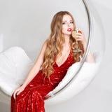 Νέα ξανθή γυναίκα στο κόκκινο φόρεμα που κρατά ένα γυαλί της άσπρης συνεδρίασης κρασιού στη διαφανή καρέκλα ενάντια στον τοίχο με Στοκ εικόνες με δικαίωμα ελεύθερης χρήσης