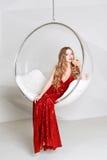 Νέα ξανθή γυναίκα στο κόκκινο φόρεμα που κρατά ένα γυαλί της άσπρης συνεδρίασης κρασιού στη διαφανή καρέκλα ενάντια στον τοίχο με Στοκ εικόνα με δικαίωμα ελεύθερης χρήσης