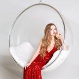 Νέα ξανθή γυναίκα στο κόκκινο φόρεμα που κρατά ένα γυαλί της άσπρης συνεδρίασης κρασιού στη διαφανή καρέκλα ενάντια στον τοίχο με Στοκ Φωτογραφίες