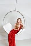 Νέα ξανθή γυναίκα στο κόκκινο φόρεμα που κρατά ένα γυαλί της άσπρης συνεδρίασης κρασιού στη διαφανή καρέκλα ενάντια στον τοίχο με Στοκ φωτογραφία με δικαίωμα ελεύθερης χρήσης