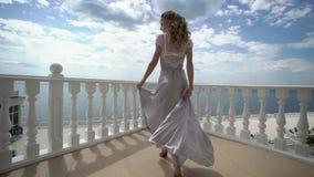 Νέα ξανθή γυναίκα lingerie στην τοποθέτηση στο πεζούλι με την άποψη θάλασσας φιλμ μικρού μήκους