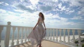 Νέα ξανθή γυναίκα lingerie στην τοποθέτηση στο πεζούλι με την άποψη θάλασσας απόθεμα βίντεο