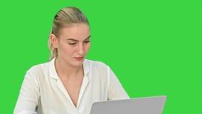 Νέα ξανθή επιχειρηματίας που εργάζεται στο φορητό προσωπικό υπολογιστή σε μια πράσινη οθόνη, κλειδί χρώματος φιλμ μικρού μήκους