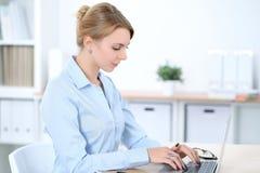 Νέα ξανθή επιχειρησιακή γυναίκα με το lap-top στο γραφείο χρυσή ιδιοκτησία βασικών πλήκτρων επιχειρησιακής έννοιας που φθάνει στο Στοκ εικόνα με δικαίωμα ελεύθερης χρήσης