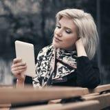 Νέα ξανθή επιχειρησιακή γυναίκα μόδας που χρησιμοποιεί τον υπολογιστή ταμπλετών στην οδό πόλεων Στοκ Φωτογραφία