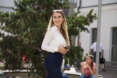 Νέα ξανθή επιχειρησιακή γυναίκα στο τζιν παντελόνι και το άσπρο πουκάμισο στοκ εικόνες