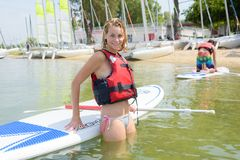 Νέα ξανθή θηλυκή τοποθέτηση ενάντια στο paddleboard στη λίμνη Στοκ Εικόνες