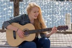 Νέα ξανθή κιθάρα παιχνιδιού γυναικών σε μια λίμνη Στοκ φωτογραφία με δικαίωμα ελεύθερης χρήσης