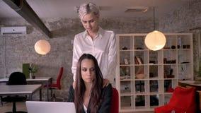 Νέα ξανθή λεσβιακή τρίβοντας γυναίκα στο σύγχρονο γραφείο κατά τη διάρκεια της εργασίας, γυναίκα που φλερτάρει με τη γυναίκα, σαγ φιλμ μικρού μήκους