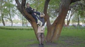 Νέα ξανθή μητέρα που κάνει μια φωτογραφία με κινητό τηλέφωνο του νέου γιου της στο δέντρο φιλμ μικρού μήκους