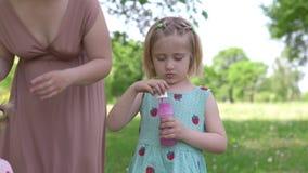 Νέα ξανθή μητέρα χίπηδων που έχει τον ποιοτικό χρόνο με τα κοριτσάκια της φυσαλίδες στις φυσώντας σαπουνιών πάρκων - οι κόρες φορ φιλμ μικρού μήκους