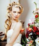 Νέα ξανθή νύφη γυναικών ομορφιάς μόνο στο εκλεκτής ποιότητας εσωτερικό πολυτέλειας με πολλά λουλούδια στοκ εικόνες με δικαίωμα ελεύθερης χρήσης