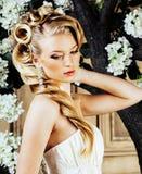 Νέα ξανθή νύφη γυναικών ομορφιάς μόνο στο εκλεκτής ποιότητας εσωτερικό πολυτέλειας με πολλά λουλούδια στοκ εικόνες