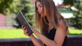 Νέα ξανθή συνεδρίαση στον πάγκο που λειτουργεί στο PC ταμπλετών Θηλυκός φοιτητής πανεπιστημίου που χρησιμοποιεί ασύρματο Διαδίκτυ φιλμ μικρού μήκους