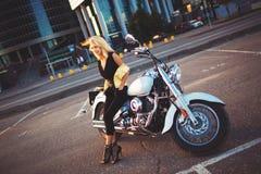 Νέα ξανθή συνεδρίαση γυναικών σε μια μοτοσικλέτα στο υπόβαθρο Στοκ Φωτογραφίες