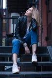 Νέα ξανθή συνεδρίαση γυναικών στα σκαλοπάτια περιστασιακό ύφος ανασκόπηση αστική Στοκ Εικόνα