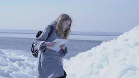 Νέα ξανθή όμορφη γυναίκα που φορά το θερμό σακάκι που στέκεται στον παγετώνα που ελέγχει με το χάρτη Καταπληκτική φύση χιονώδους απόθεμα βίντεο