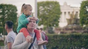 Νέα οδηγώντας κόρη μπαμπάδων στους ώμους στο θερινό πάρκο οικογενειακό ευτυχές & απόθεμα βίντεο