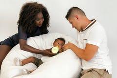 Νέα οικογένεια Γονείς που ταΐζουν ένα παιδί νηπίων με το γάλα Τουαλέτα συζύγων στοκ εικόνα