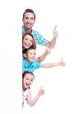Νέα οικογένεια με ένα έμβλημα που παρουσιάζει τον αντίχειρας-επάνω στοκ εικόνες