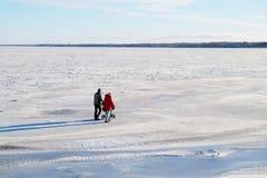 Νέα οικογένεια με ένα μικρό παιδί που περπατά στον πάγο Στοκ Φωτογραφίες