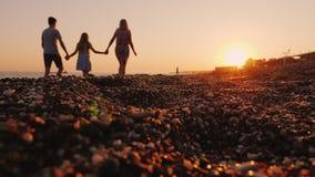 Νέα οικογένεια με ένα παιδί που περπατά κατά μήκος της παραλίας στο ηλιοβασίλεμα, στο πρώτο πλάνο μια παραλία χαλικιών απόθεμα βίντεο