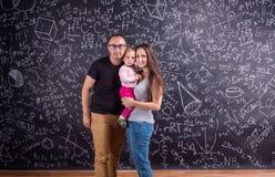 Νέα οικογένεια με λίγη κόρη ενάντια στο μεγάλο πίνακα Στοκ Φωτογραφία