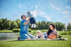 Νέα οικογένεια με τα παιδιά που έχουν τη διασκέδαση στη φύση στοκ φωτογραφία με δικαίωμα ελεύθερης χρήσης