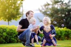 Νέα οικογένεια με τα παιδιά μικρών παιδιών τους που φυσούν τις φυσαλίδες σαπουνιών στοκ εικόνες με δικαίωμα ελεύθερης χρήσης