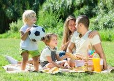 Νέα οικογένεια με τα παιδιά που έχουν το πικ-νίκ υπαίθριο Στοκ φωτογραφία με δικαίωμα ελεύθερης χρήσης