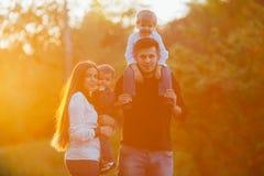 Νέα οικογένεια με τα παιδιά που περπατούν στο πάρκο Πατέρας, μητέρα και δύο γιοι Στοκ Εικόνα