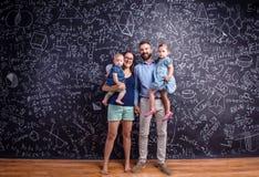 Νέα οικογένεια με δύο μικρές κόρες ενάντια στο μεγάλο πίνακα Στοκ Εικόνες