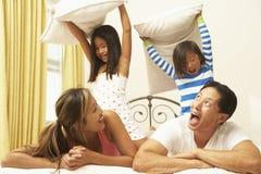 Νέα οικογένεια που έχει την πάλη μαξιλαριών Στοκ Φωτογραφίες