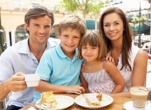 Νέα οικογένεια που απολαμβάνει το φλιτζάνι του καφέ και το κέικ Στοκ φωτογραφία με δικαίωμα ελεύθερης χρήσης