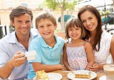 Νέα οικογένεια που απολαμβάνει το φλιτζάνι του καφέ στοκ εικόνα με δικαίωμα ελεύθερης χρήσης