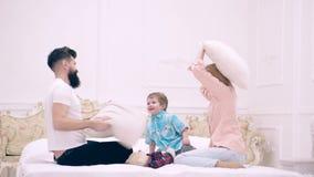 Νέα οικογένεια που είναι εύθυμη στο σπίτι Οικογένεια που έχει την αστεία πάλη μαξιλαριών στο κρεβάτι Γονείς που περνούν το ελεύθε φιλμ μικρού μήκους