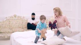 Νέα οικογένεια που είναι εύθυμη στο σπίτι Οικογένεια που έχει την αστεία πάλη μαξιλαριών στο κρεβάτι στο σπίτι Γονείς που περνούν φιλμ μικρού μήκους
