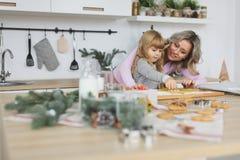Νέα οικογένεια που κατασκευάζει τα μπισκότα στο σπίτι τρόφιμα, οικογένεια, Χριστούγεννα, hapiness και έννοια ανθρώπων - χαμογελών Στοκ Φωτογραφίες